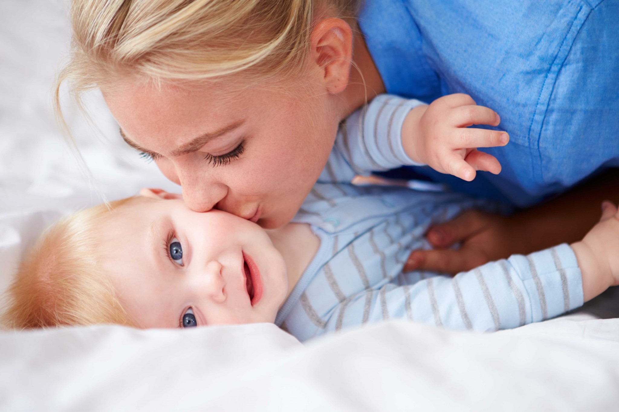 mother kissing surrogate baby