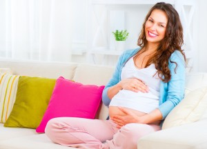 Pregnant Happy smiling Woman sitting on a sofa and caressing her